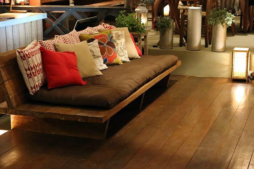 Detalhes da decoração: belíssimas almofadas em sofá despojado no centro do salão